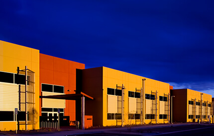 An industrial buildings having along the black city streets and with an orange and yellow exterior coatings with the use of the complete blasting facilities.